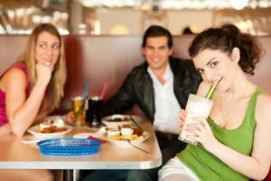 Drei Menschen die je einen Proteinshake trinken oder vor sich stehen habe.